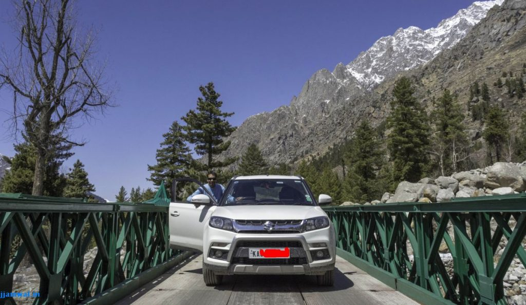 G posing with his car on a bridge near Chitkul